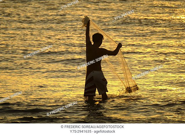 Fisherman is in the water and fishing with a net,Kuta beach,Bali,Indonesia