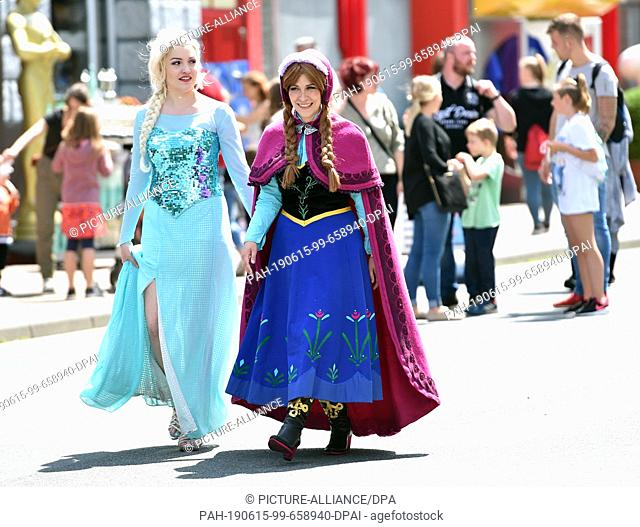 15 June 2019, North Rhine-Westphalia, Bottrop: Cosplayer disguised as Elsa (l) and Anna (r) walk through the Movie Park during the 2nd Cosplay Day