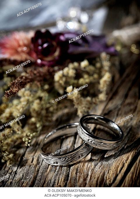 White gold wedding rings with Celtic design and wild dried flowers on rustic background, artistic marriage still life
