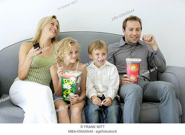 Family with 2 children is sitting with popcorn on sofa and is watching TV, amused