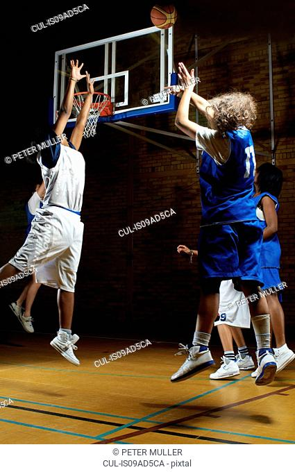 Basketball players jumping for ball