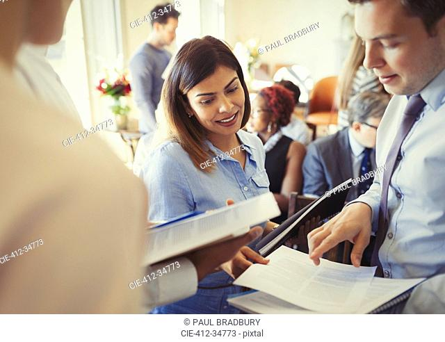 Business people discussing paperwork at business conference