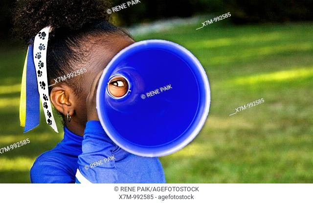 Tunnel vision  A little girl playfully peers through a megaphone
