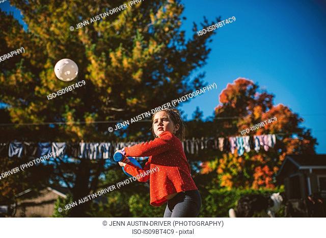 Girl preparing to hit baseball ball in garden