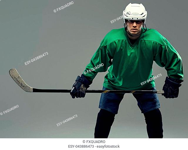 Portrait of a professional hockey player wearing full gear and hockey stick. Isolated on a gray background