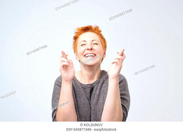 Happy matureredhead female eager to win competition, keeps fingers crossed as waits for results, smiles broadly, shows white perfect teeth, poses in studio