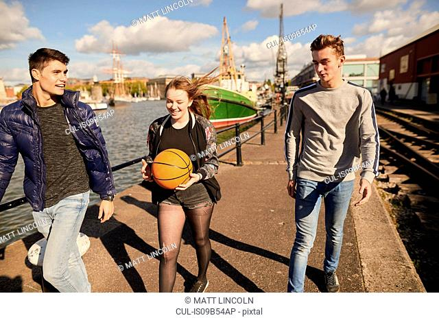 Three friends walking beside river, young woman carrying basketball, Bristol, UK