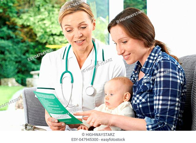 Health Visitor Giving Mother Leaflet With Advice On Baby