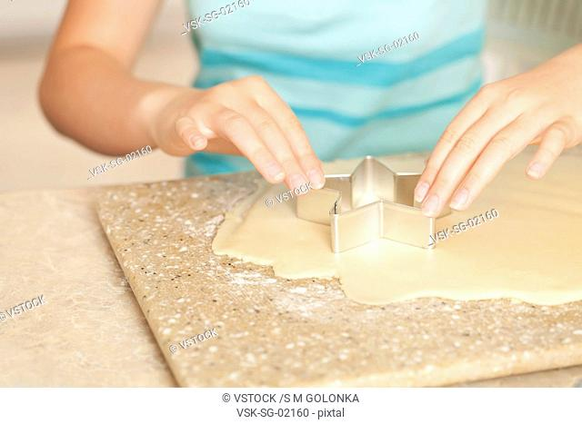 USA, California, Lawndale, Close-up of girl 10-11 using pastry cutter on dough