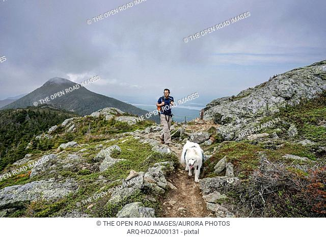 Man hikes with dog on Avery Peak above Flagstaff Lake along the Appalachian Trail in Maine's Bigelow Mountains