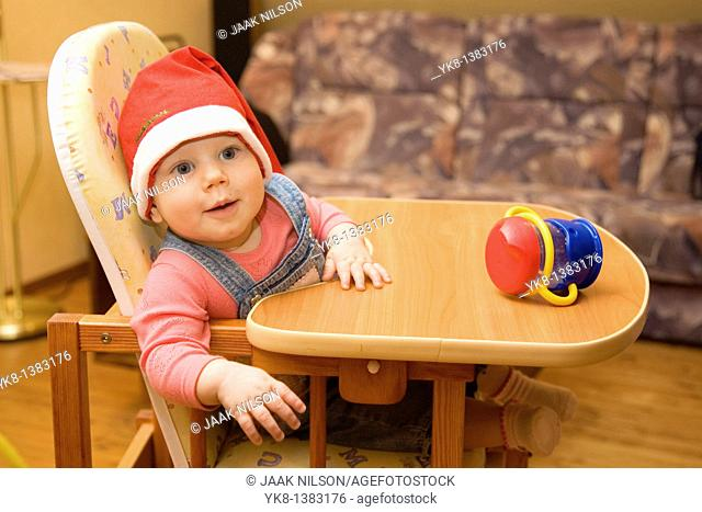 Happy Smiling Eight Month Old Infant Girl with Cup and Christmas Red Hat in High Chair