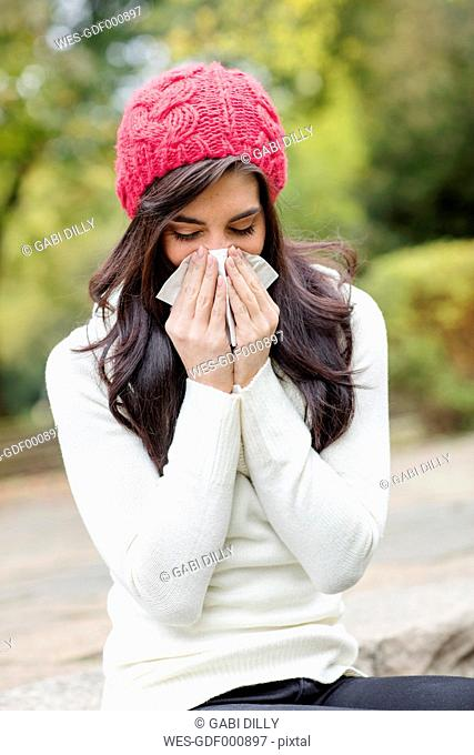 Young woman wearing red woolly hat blowing her nose