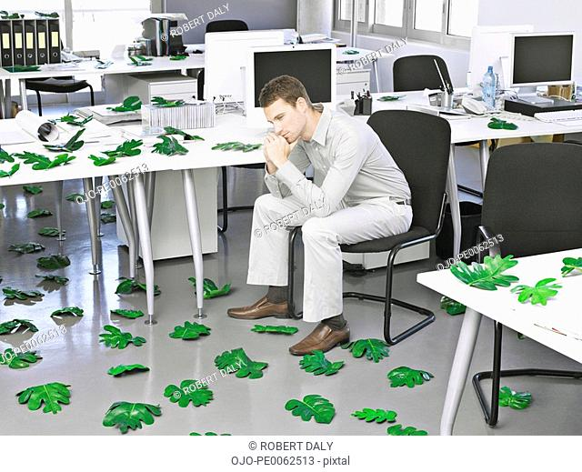 Businessman in modern office surrounded by leaves