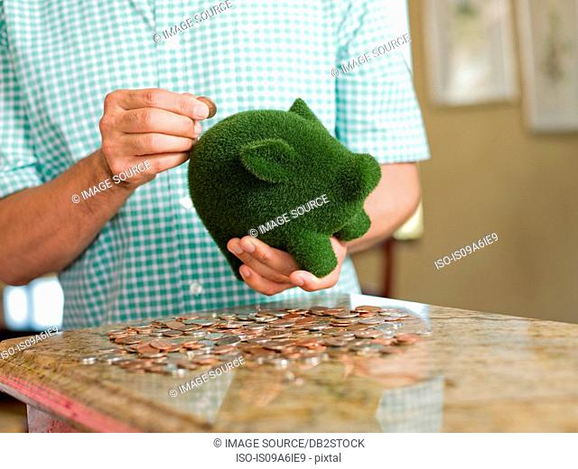 Man putting coins in green piggy bank
