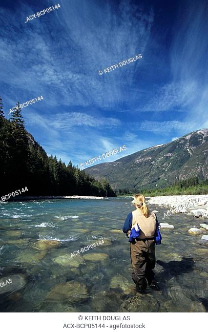 Lady flyfisher, fishing for steelhead, Dean river, Central Coast, British Columbia, Canada