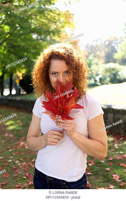 Portrait of a woman with red, curly hair holding autumn coloured leaves; Burnaby, British Columbia, Canada