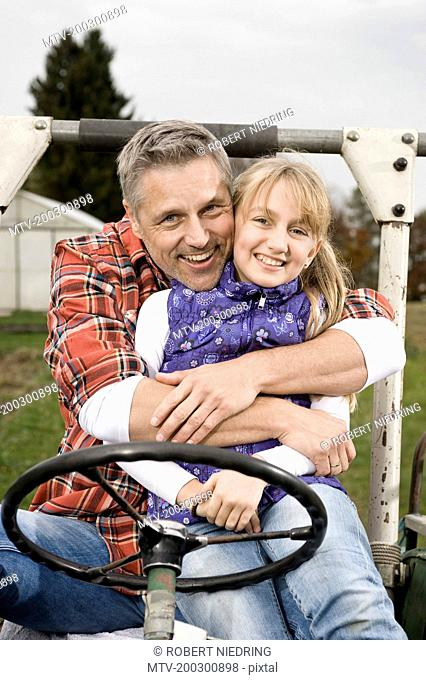 Farmer hugging daughter on tractor