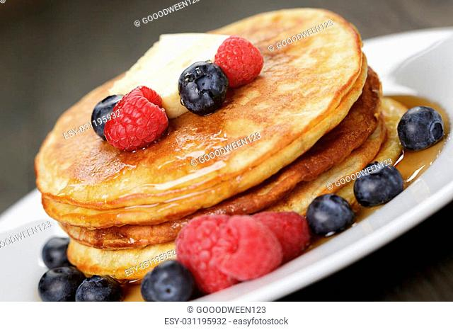 Pancakes with raspberry, blueberry and maple syrup, on oak wooden table