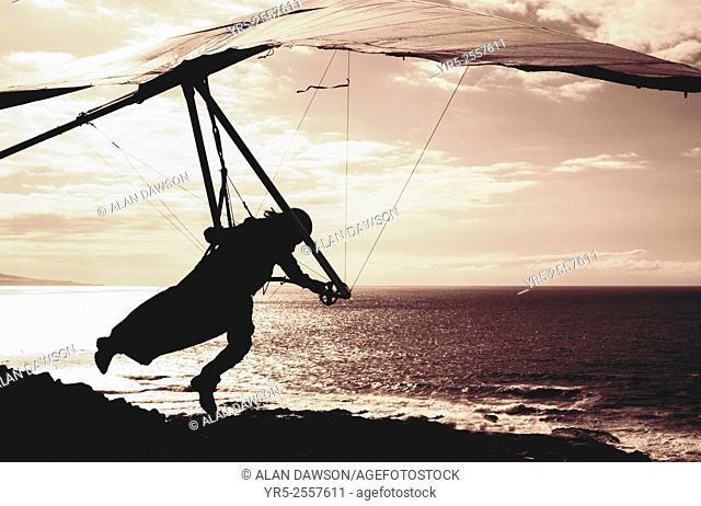Las Palmas, Gran Canaria, Canary Islands, Spain. Hang Glider taking off over Atlantic Ocean in Las Palmas