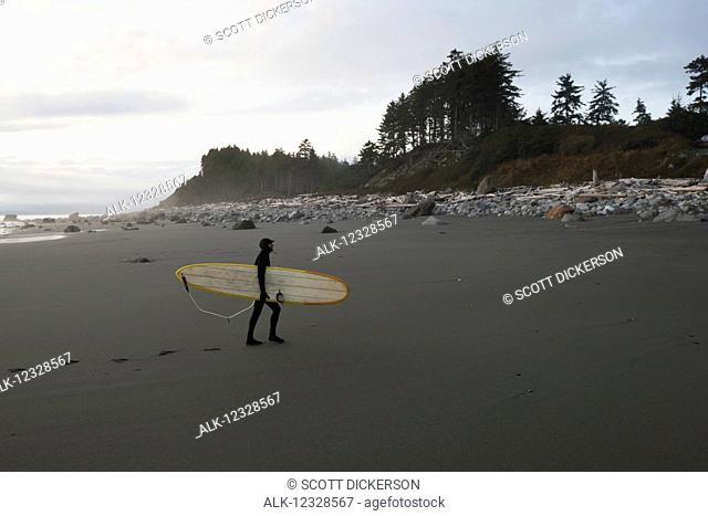 Surfer with his board leaving footprints on the beach, Southeast Alaska; Yakutat, Alaska, United States of America