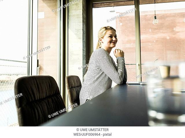 Smiling young woman at desk in office