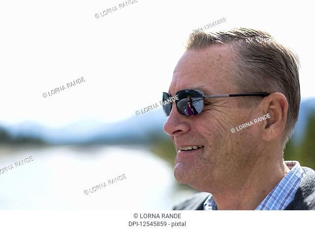 Portrait of a man wearing sunglasses and looking away; Kananaskis, Alberta, Canada