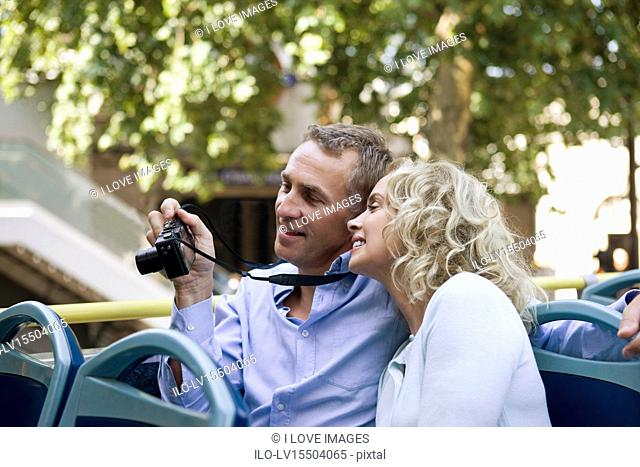 A middle-aged couple sitting on a sightseeing bus, holding a camera