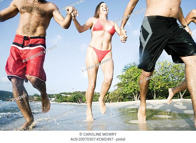 Mid adult woman running with her friends on the beach