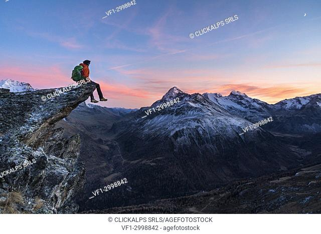 An hiker on a rock in Viola valley with a panoramic view to the Alps at sunset. Valdidentro, Valtellina, Lombardy, Italy