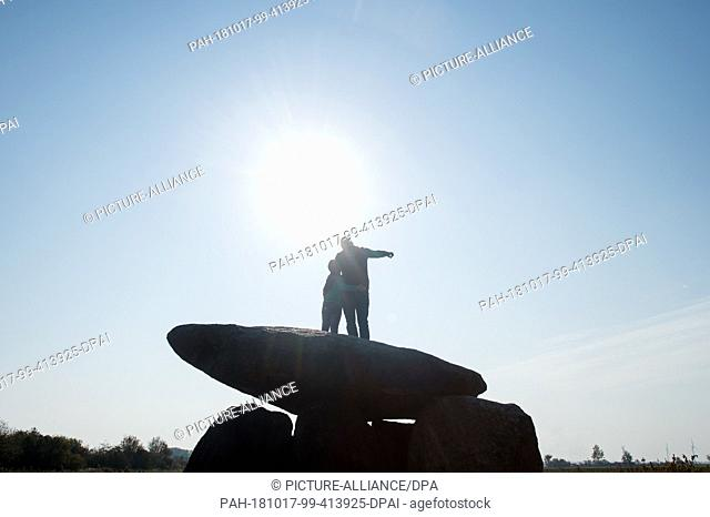 17 October 2018, Saxony-Anhalt, Drosa: 17 October 2018, Germany, Drosa: A father shows his son the surrounding countryside and stands on the big stone tomb...