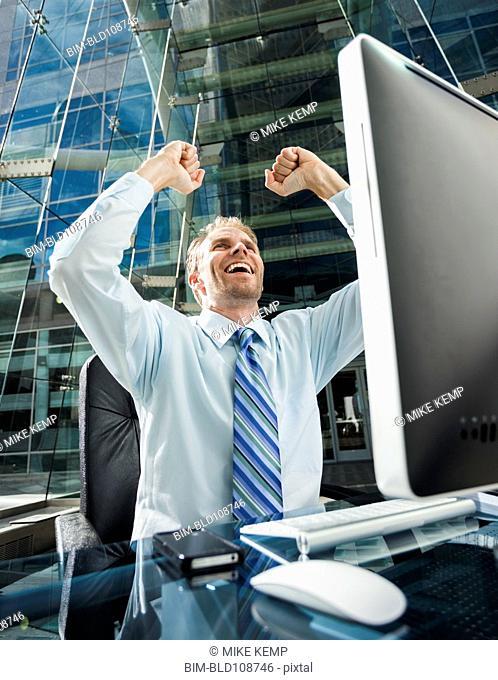 Caucasian businessman cheering at computer