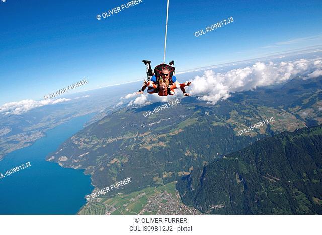 Tandem sky divers free falling as parachute released, Interlaken, Berne, Switzerland