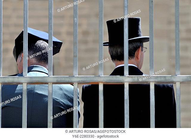 A guardia civil (policeman) and a man with top-hat behind bars in San Lorenzo de El Escorial (Madrid), Spain