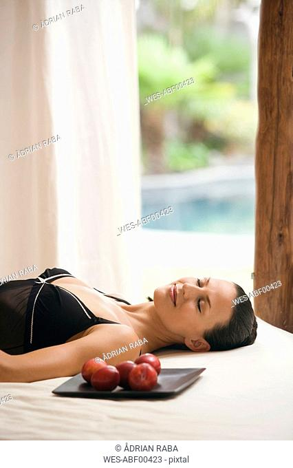 Young woman wearing neglige, relaxing on bed alongside tray with plums