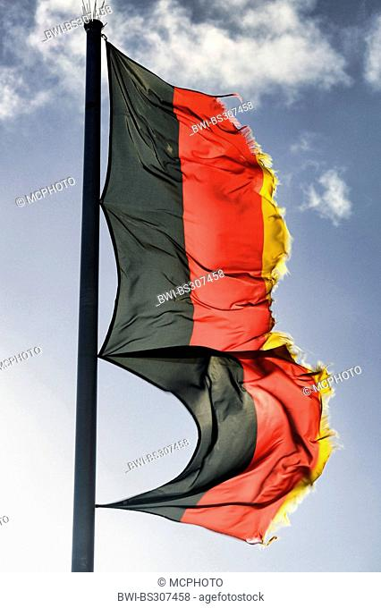 ragged german national flag waving in the wind
