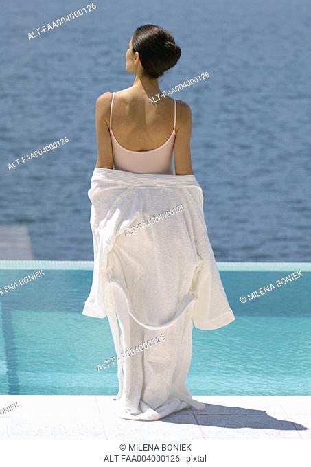 Woman standing overlooking water, bathrobe off shoulders