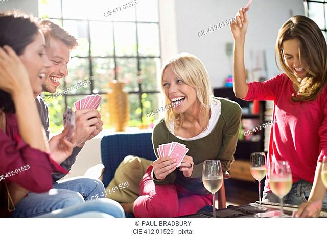 Friends playing card game in living room
