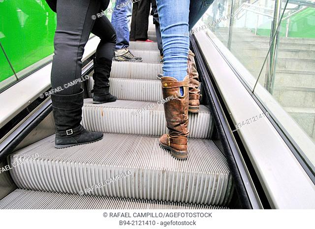 Girls with boots on escalator. Subway station Barcelona. Catalonia. Spain