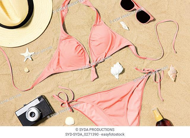 bikini, hat, camera and sunglasses on beach sand