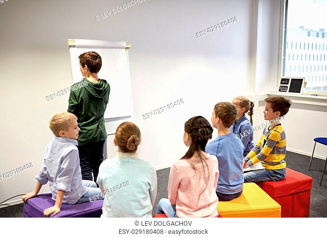 education, elementary school, learning and people concept - student boy with marker writing on flip board