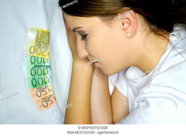 Economic crisis - woman sleeps with cash under the pillow