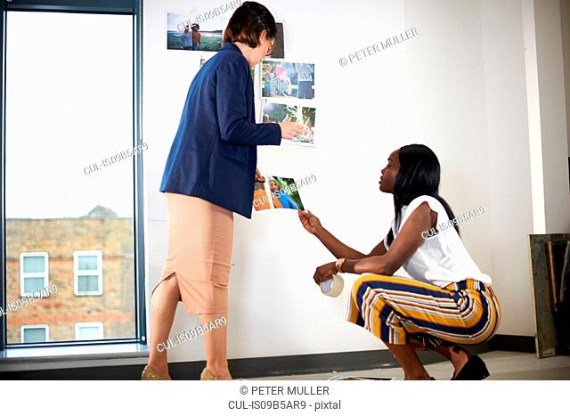 Colleagues in office sticking photographs on wall