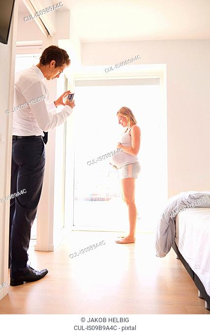 Man taking smartphone photograph of pregnant girlfriend in bedroom