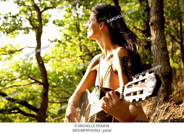 Young woman playing guitar in forest
