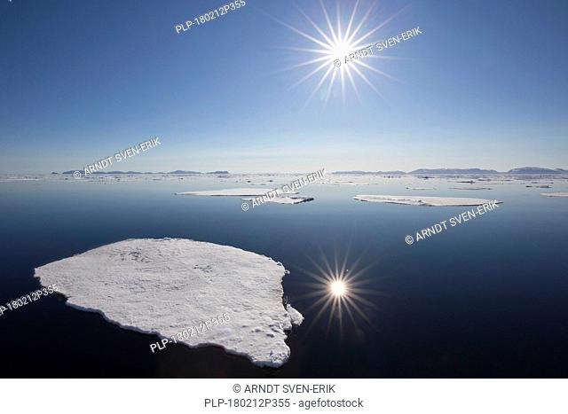 Midnight sun over the Arctic Ocean with drifting ice floes, north of the Arctic Circle at Nordaustlandet, Svalbard / Spitsbergen, Norway