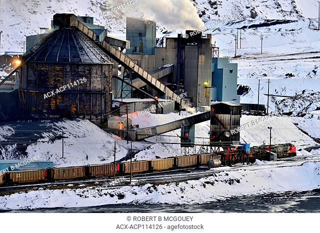 A freight train loading coal ore from a coal processing plant in the foothills of the rocky mountains near Cadomin Alberta Canada
