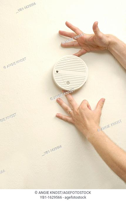 Man's hands placing a smoke detector on the wall