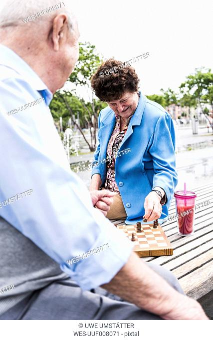 Senior couple sitting on a bench playing chess