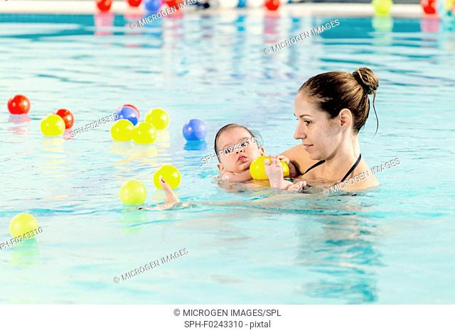 Baby boy with mother in swimming pool