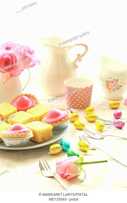 Easter table with sweet eggs, pink roses and fresh cakes